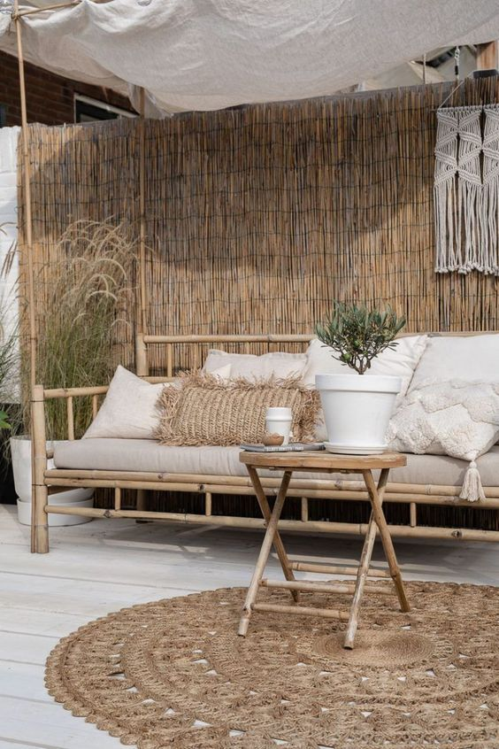 a tropical deck with a roof, a bamboo sofa, a folding side table of bamboo, a jute rug and potted greenery plus macrame hanging