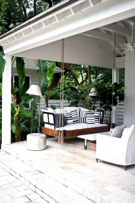 a tropical terrace with a hanging daybed with printed pillows, a coffee table and a white chair plus lots of tropical greenery around