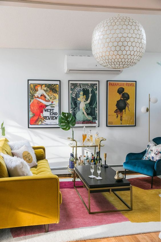 a vibrant living room with a bold rug, a mustard sofa and a navy chair, a chic coffee table and a bar cart plus a bold gallery wall