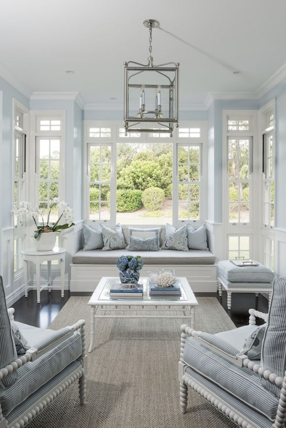 a vintage coastal interior in light blue and white, with lots of French windows and much light thanks to them, refined white furniutre, a chandelier and printed pillows