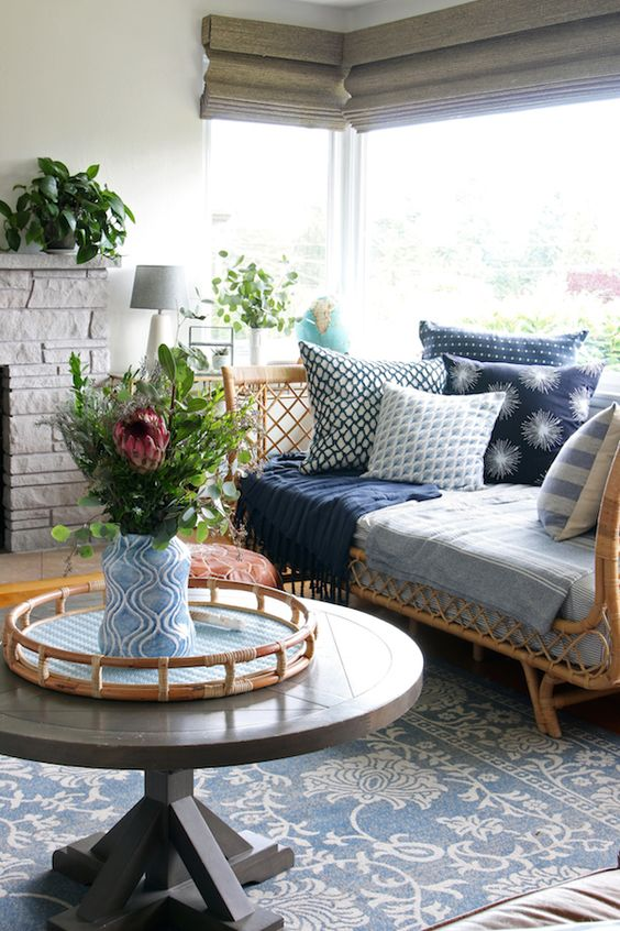 a vintage eclectic space with a corner window, a woven daybed with printed bedding and pillows, a stone clad fireplace and a round table