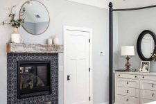 a vintage farmhouse bedroom with a black metal canopy bed, a built-in fireplace with black tiles, a round mirror, a white dresser and a wooden chandelier