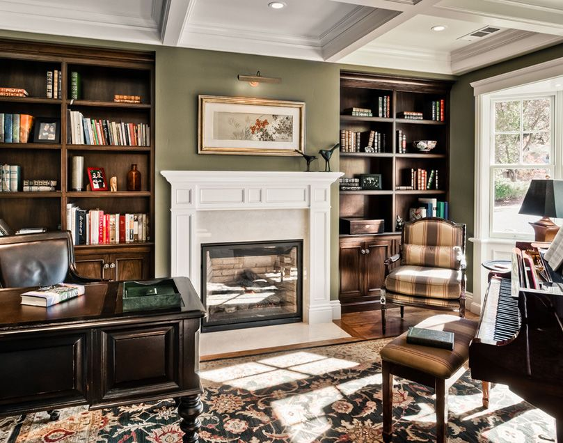 a vintage home office with green walls, built in dark stained shelves, a black vintage desk, a black chair, a piano and some stools