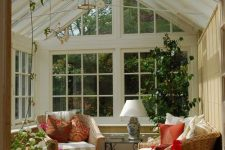 a vintage-inspired rustic sunroom with French windows and whole walls, a glass slated roof, potted blooms and a tree and colorful touches