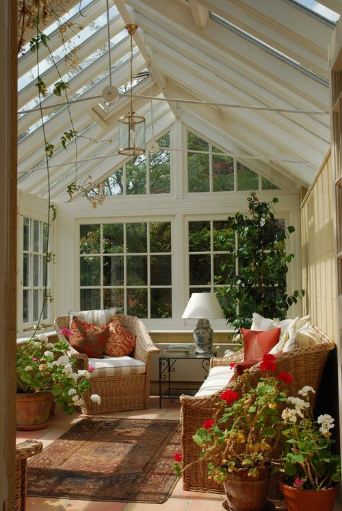 a vintage inspired rustic sunroom with French windows and whole walls, a glass slated roof, potted blooms and a tree and colorful touches