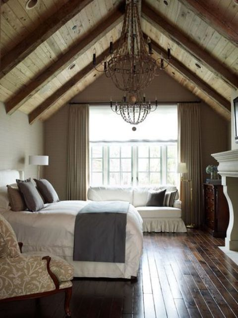 a vintage rustic bedroom with a wodoen slanted ceiling, a vintage fireplace, a bed with grey and white bedding, a sofa, a vintage chair and vintage chandeliers