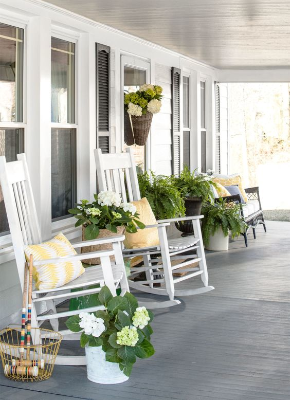 a vintage rustic porch with white rockers and a black vintage bench, potted plants and blooms plus printed pillows is a chic idea