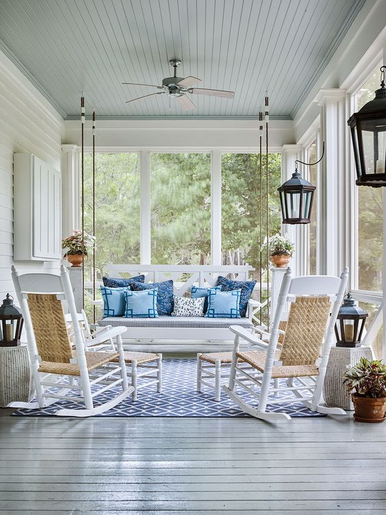 a vintage screened porch with a white hanging bench, white rockers, footrests, blue pillows and potted plants is amazing