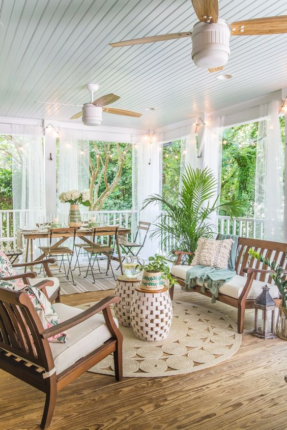 a vintage tropical screened porch with a dining set with folding furniture, wooden chairs and a bench, woven side tables and potted plants