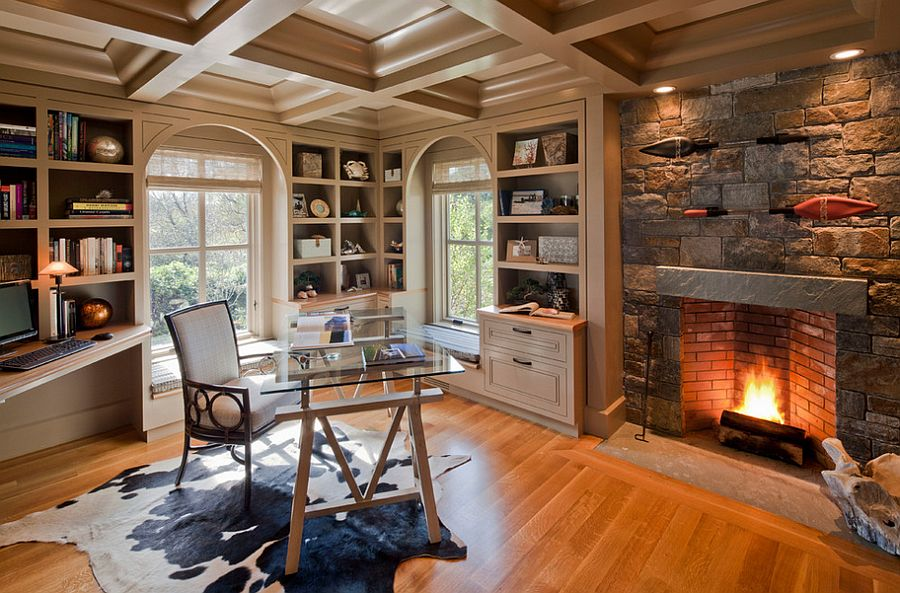 a welcoming and cozy home office with a stone clad fireplace, built in shelves and niche shelves, a glass desk and a white chair
