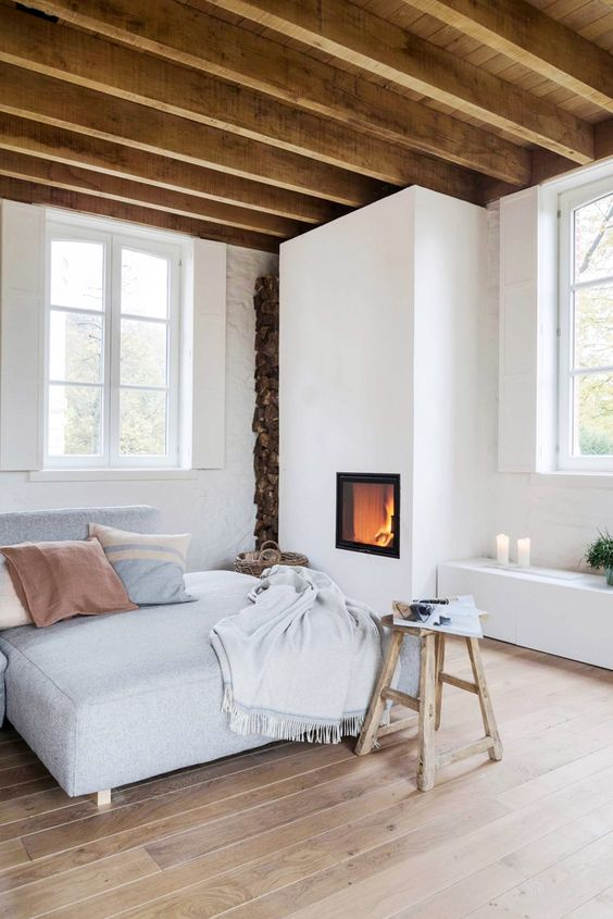 a welcoming and neutral-looking bedroom with a built-in fireplace, a bed, a stool, a storage unit with candles and wooden beams on the ceiling