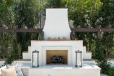 a welcoming coastal terrace with a white stucco fireplace, a white wicker sofa and an ottoman, candle lanterns and lots of greenery