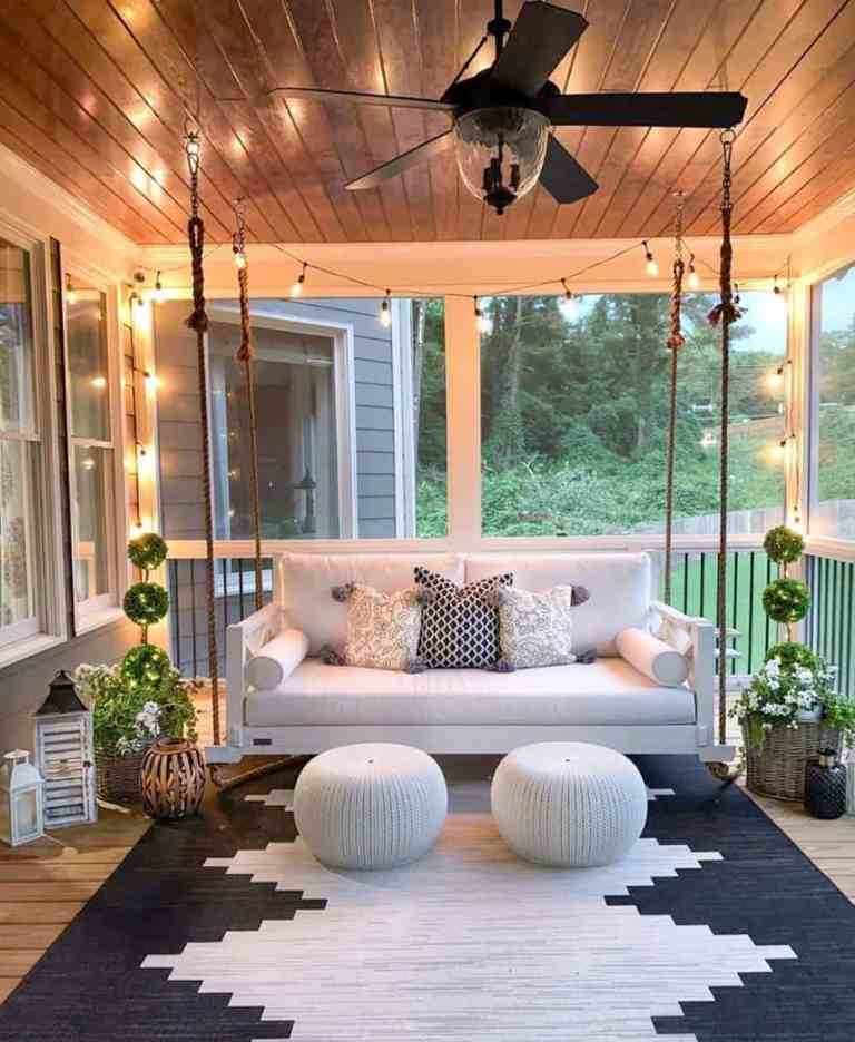 a welcoming farmhouse porch with a hanging sofa, white ottomans, a graphic rug, potted greenery and candle lanterns