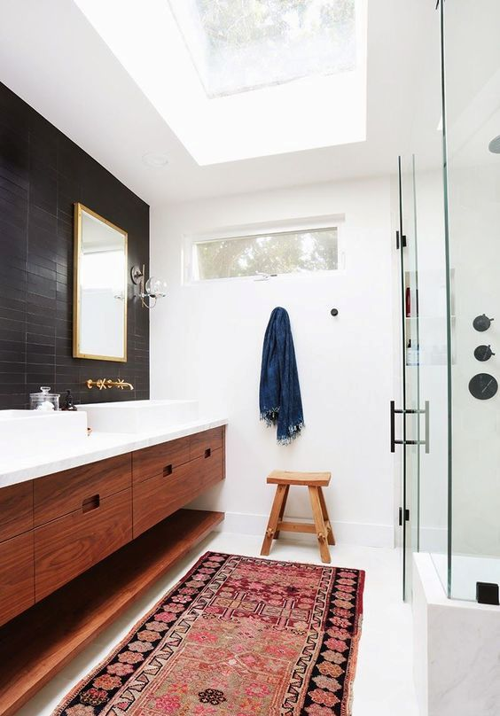 a welcoming mid-century modern bathroom with black and white tiles, a shower space, a double stained vanity, metallic fixtures