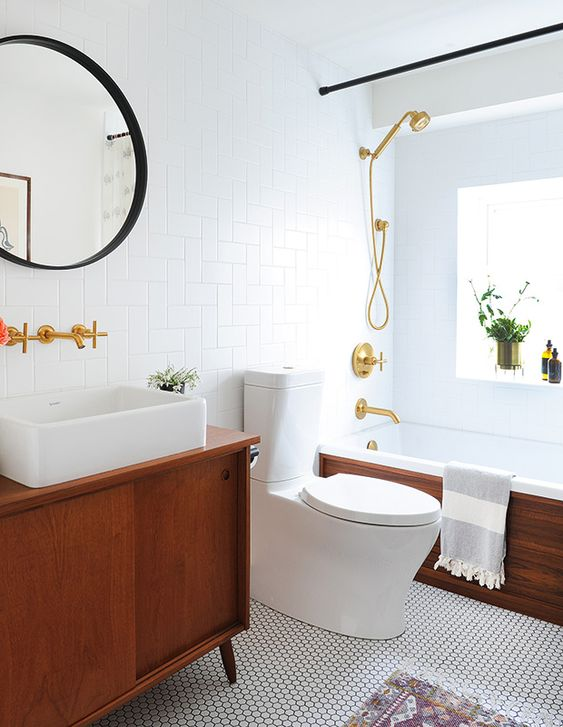 a welcoming mid-century modern bathroom with penny and woven tiles, a rich-stained vanity and a bathtub clad with stained wood, gold fixtures