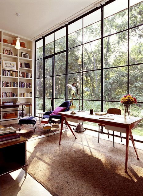 a welcoming mid-century modern home office with a glazed wall, a lightweight desk, a leather chair and a navy one, a book storage unit