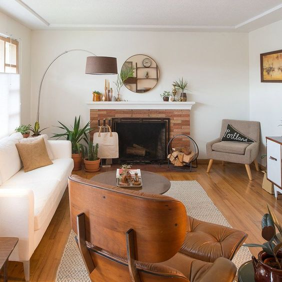 a welcoming mid-century modern living room with a creamy sofa, a tan and an maber chair, a coffee table, a fireplace clad with brick and a cool floor lamp