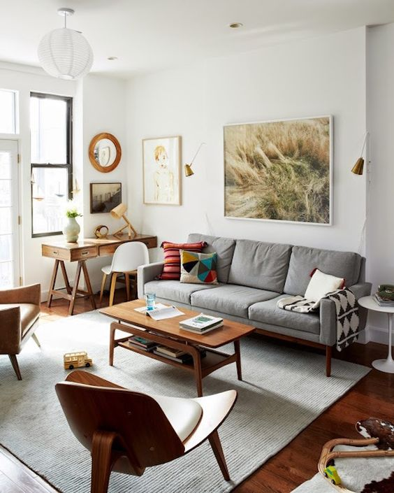 a welcoming mid-century modern living room with a grey sofa, a stained table and plywood chairs, a small desk and lovely artworks