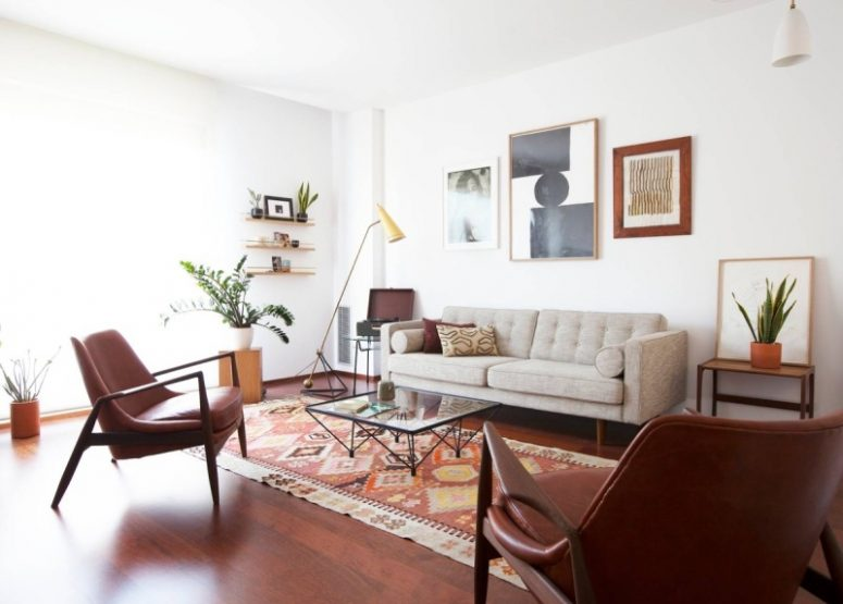 a welcoming mid-century modern living room with a grey sofa, burgundy leather chairs, a chic gallery wall, open shelves, printed pillows and a rug