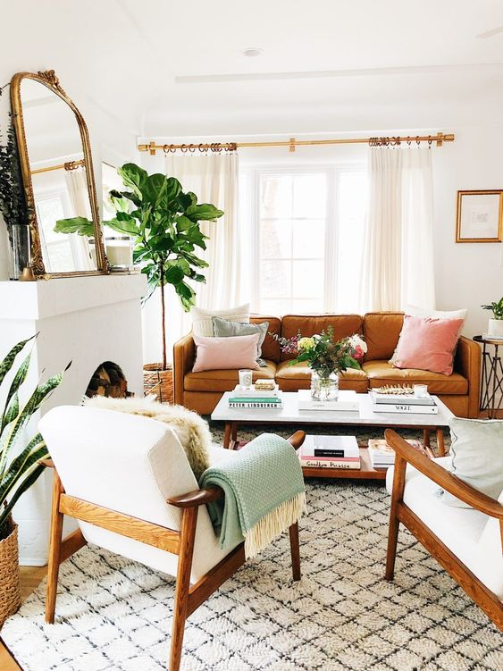 a welcoming mid-century modern lviing room with a non-working fireplace, an amber leather sofa, white chairs, a low coffee table, a mirror and pastel pillows