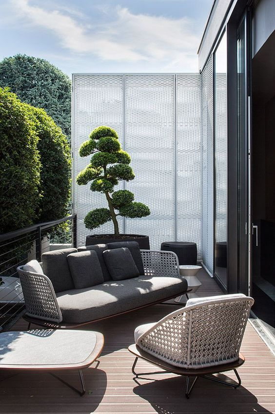 a welcoming modern balcony with a privacy screen, some woven furniture with hairpin legs, a low table and potted greenery is chic