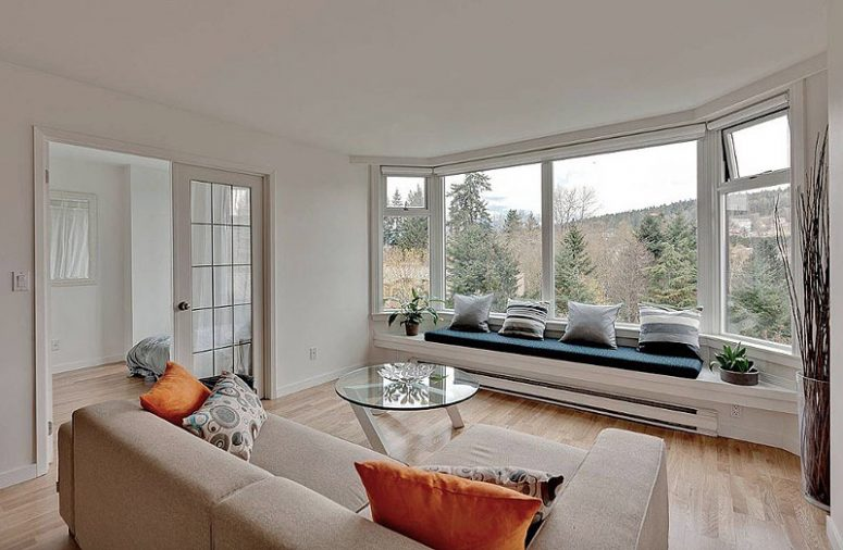 a welcoming modern living room with a large bow window, a built-in daybed with pillows, a neutral sofa and a chic glass table
