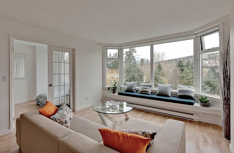 a welcoming modern living room with a large bow window, a built in daybed with pillows, a neutral sofa and a chic glass table