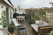 a welcoming modern terrace with a wooden deck, wooden furniture, metal round tables, greenery interweaving the screen