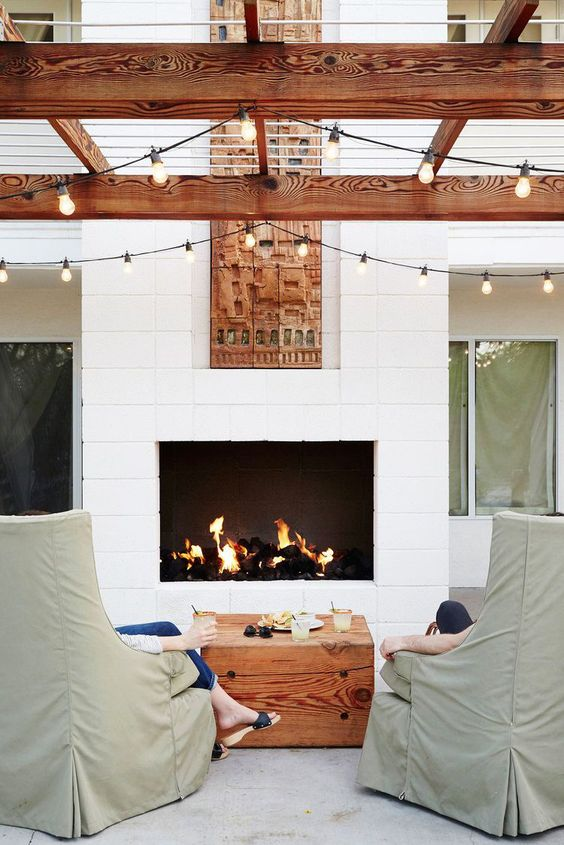 a welcoming outdoor space with a white fireplace clad with stucco, green chairs, a wood slab table and string lights over the space