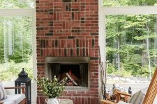 a welcoming screened porch with a brick fireplace, simple stained wood furniture, neutral textiles and a faceted pendant lamp