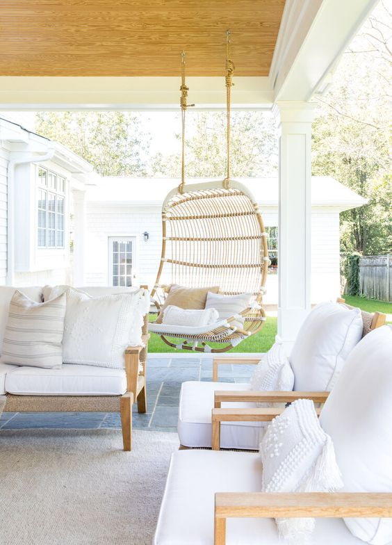 a welcoming terrace with neutral furniture, a hanging rattan chair and neutral textiles is a heavenly relaxing and gorgeous place to be