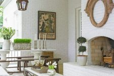 a welcoming white vintage outdoor space with brick walls and a fireplace, with a rusitc dining set, a small table and a wicker sofa, lots of blooms and greenery