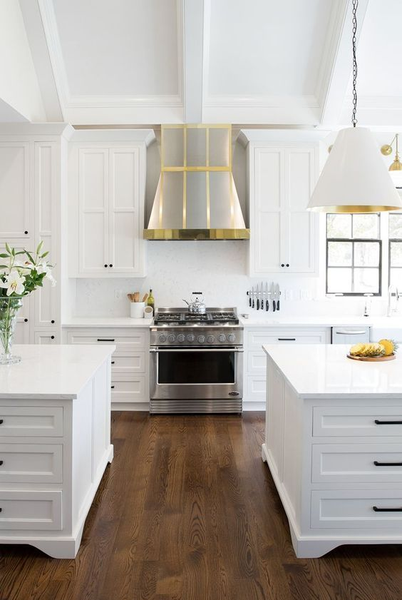 a white farmhouse kitchen with shaker style cabinets, black handles, silver hood with gold touches, white and gold lamps and chromatic appliances