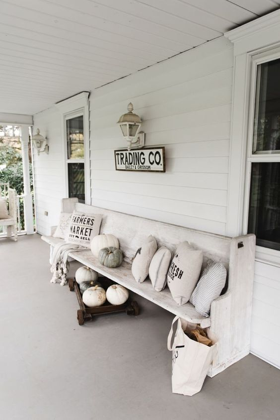 a white farmhouse porch styled for the fall, with a whitewashed bench, printed pillows, pumpkins and vintage sconces on the wall