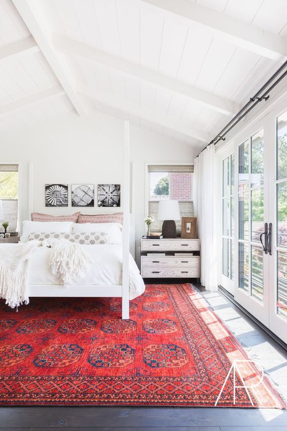 a white mid-century modern bedroom with a canopy bed, whitewashed nightstands, a black and white gallery wall, a red printed rug and a glazed wall