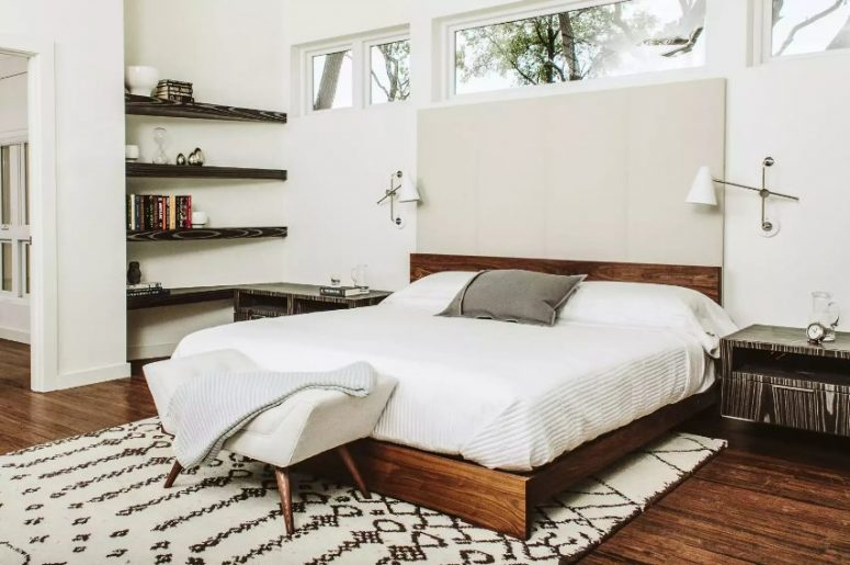 a white mid-century modern bedroom with dark built-in shelves, a rich-stained bed, a white seat, nightstands and narrow and long windows