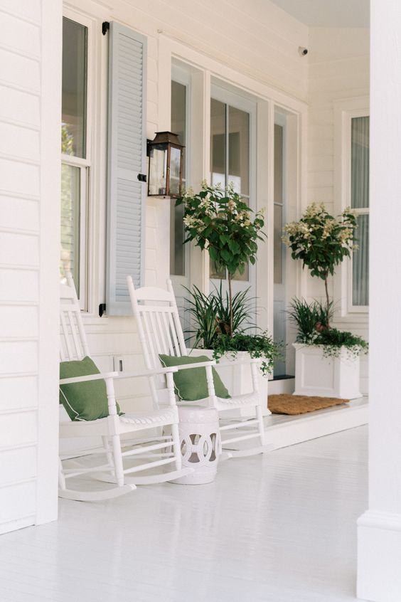 a white rustic summer porch with white furniture and planters with blooms and greenery, green pillows and a side table is very airy