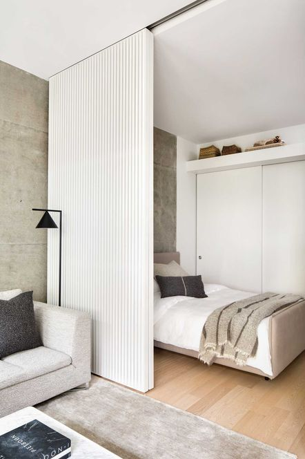 a white wooden slab sliding door separates a small sleeping space from the rest of the room and makes it more private