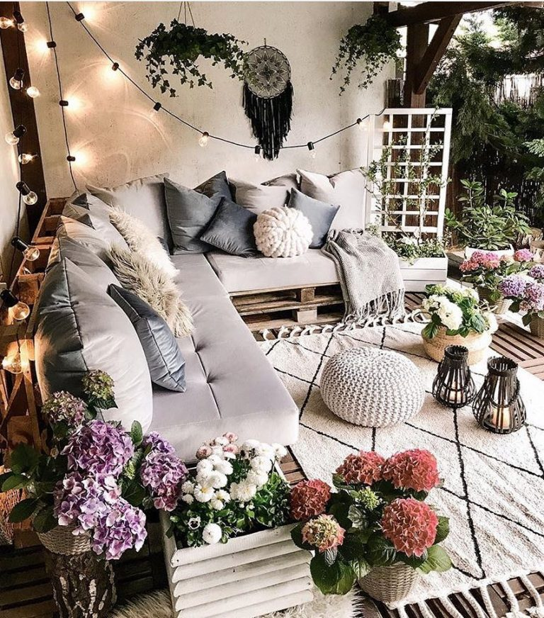 a wonderful outdoor space with a pallet corner bed, lots of blooms, string lights, a dream catcher, neutral pillows and upholstery and greenery
