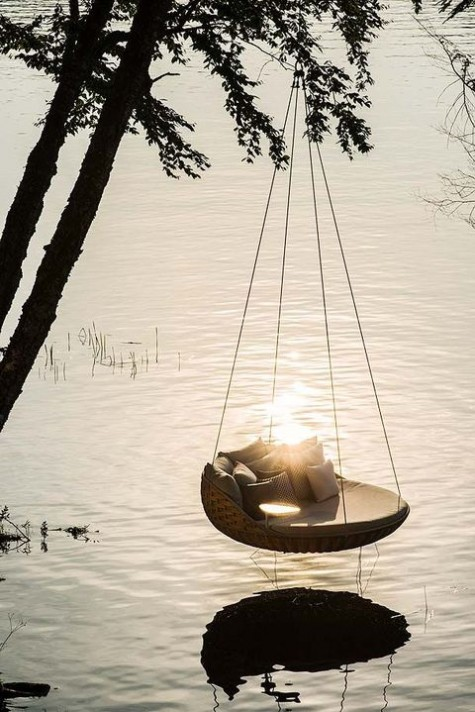 a woven round outdoor hanging bed with lots of pillows hung on a tree above water is all about relaxation and calmness
