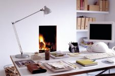 an airy home office in white, with a planked floor, a built-in fireplace, a sleek and airy desk, a leather chair and built-in shelves
