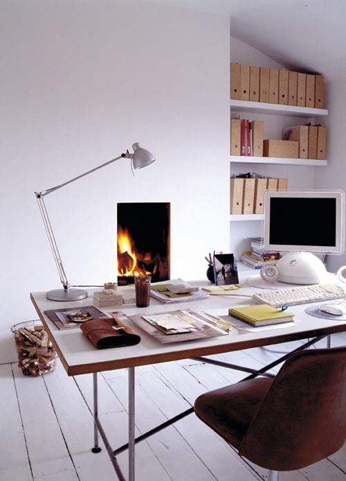 an airy home office in white, with a planked floor, a built in fireplace, a sleek and airy desk, a leather chair and built in shelves
