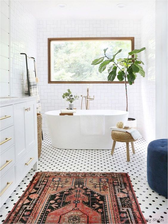 an airy mid-century modern bathroom with a penny tile floor, a white vanity and a white tub, a printed rug and a blue ottoman