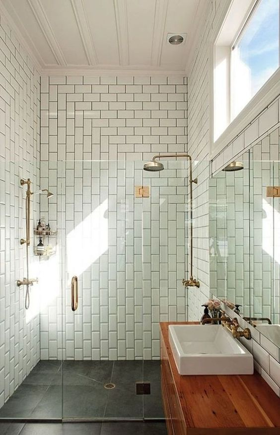 an airy mid-century modern bathroom with grey and white tiles, a stained vanity, metallic appliances and a sink