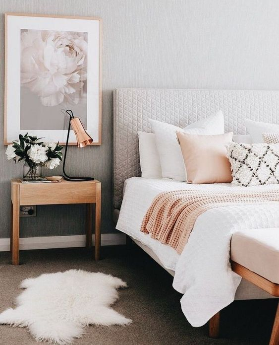 an airy mid-century modern bedroom with grey walls and a tan floor, a grey upholstered bed, neutral bedding, a little nightstand, a copper lamp and a chic print