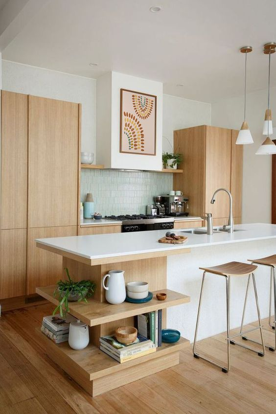 an airy mid-century modern kitchen with light-stained cabinets, a white kitchen island with open shelves, a green tile backsplash and pendant lamps
