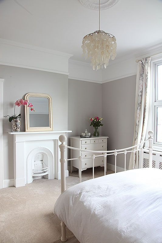 an airy neutral bedroom with a built-in fireplace, a white metal bed, a chandelier of mother of pearl, a mirror, a white dresser and printed textiles
