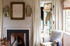 an eclectic vintage bdroom with pink walls, a planked chevron accent and a fireplace, neutral and pastel textiles, a black vintage bed