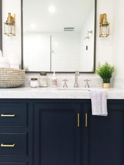 an elegant bathroom with a navy vanity, gold handles, gold sconces, chromatic faucets looks very chic and very bold and eye-catchy