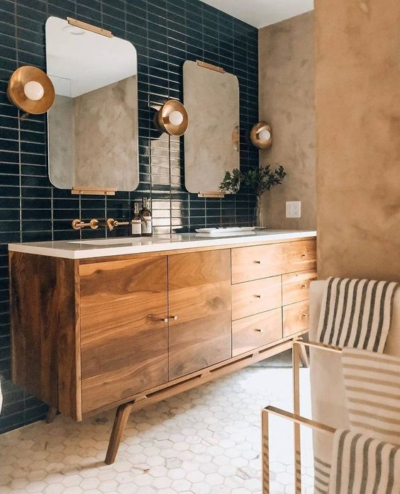 an elegant bathroom with navy skinny and white hexagon tiles, a rich stained vanity, cool mirrors and lamps is amazing